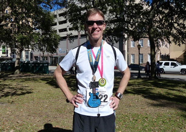 Mike Sohaskey sporting medals from 2014 Mississippi Blues & First Light marathons