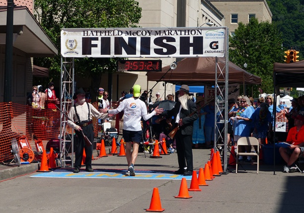 Mike Sohaskey high-fiving Hatfield & McCoy at finish
