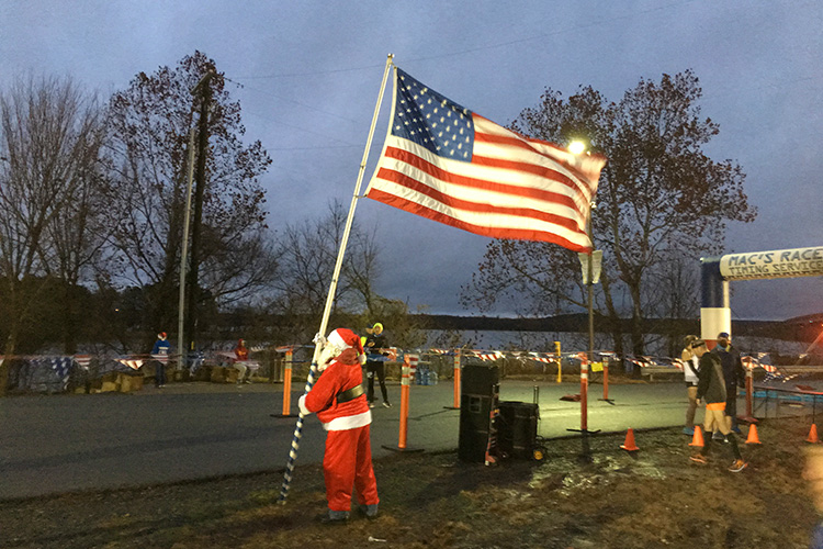Santa holding the American flag at 3 Bridges Marathon start line