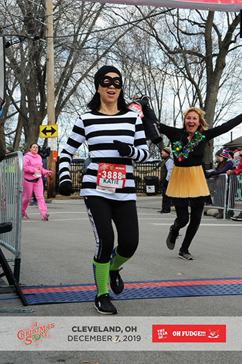Katie Ho crossing finish line of A Christmas Story 5K Run