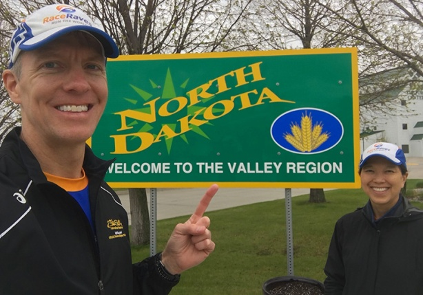 Mike Sohaskey & Katie Ho in front of North Dakota welcome sign