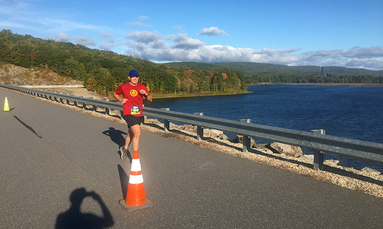 Ken S running across the Surry Mountain Dam during mile 11 of the Clarence DeMar Marathon