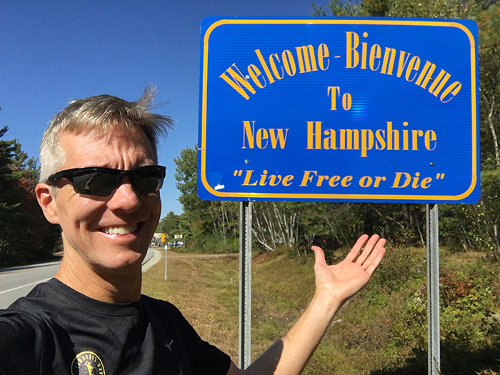 Mike Sohaskey by Welcome to New Hampshire sign