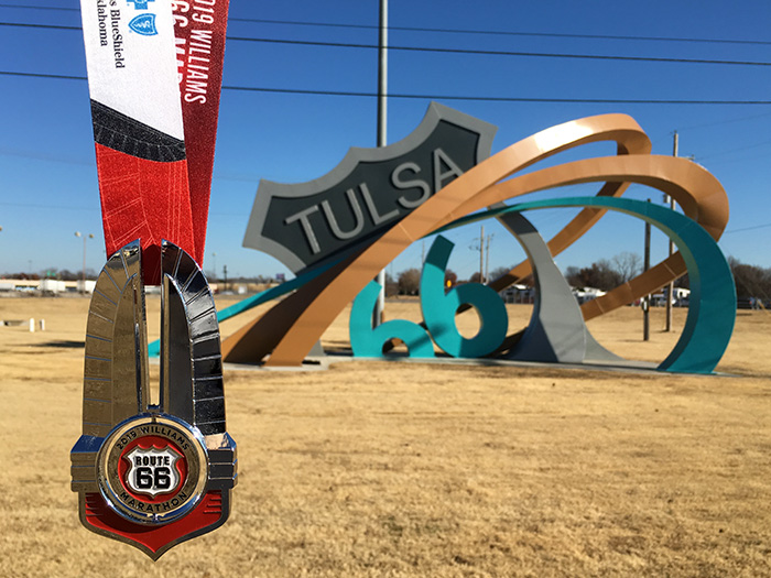 Route 66 medal in front of the Tulsa Route 66 Rising sculpture