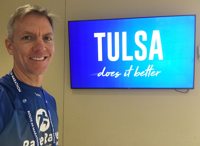 "Mike Sohaskey in front of ""Tulsa does it better"" sign"