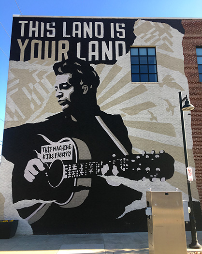 This Land is Your Land mural on wall of Woody Guthrie Center in Tulsa